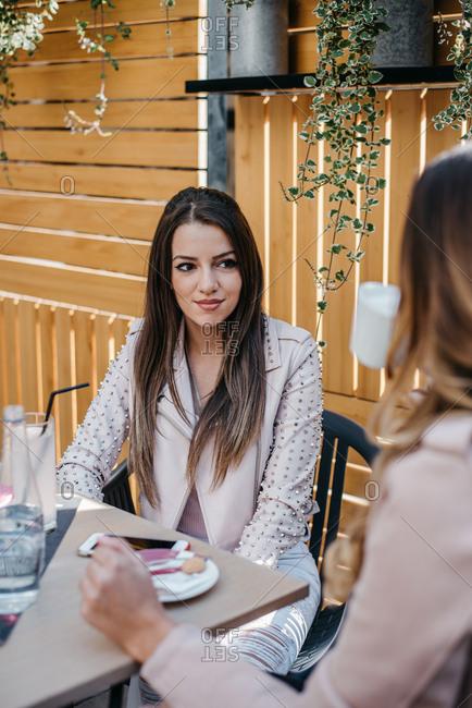 Two girlfriends talking in a coffee shop