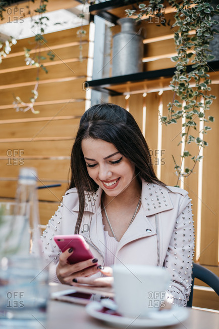 Pretty young woman using her smartphone and smiling in a coffee shop
