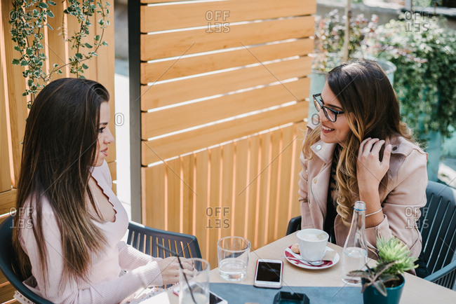 Two female friends having a conversation outside in a garden of a coffee shop