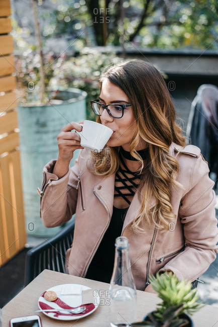 Young lady drinking her coffee in a coffee bar