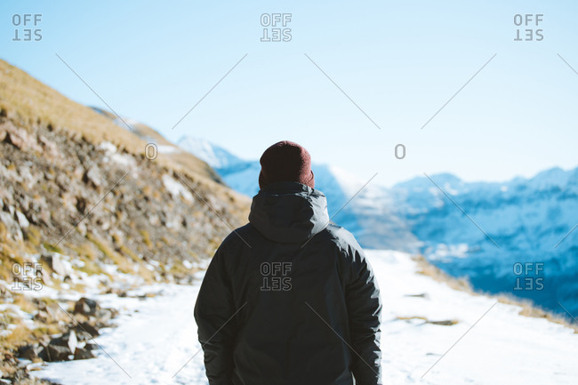 Person on black rain jacket watching the snowy mountains in Pyrenees
