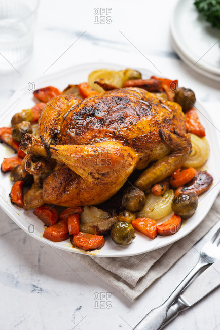 Roasted crispy chicken served on bed of roasted vegetables