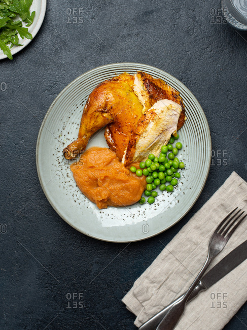 Roasted chicken pieces served on plate with green peas and sweet potato mash