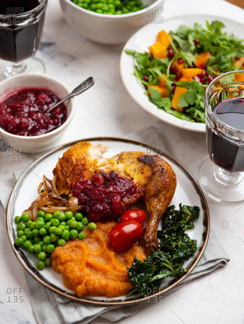 Thanksgiving dinner with roasted chicken served on plate with green peas and cranberry sauce