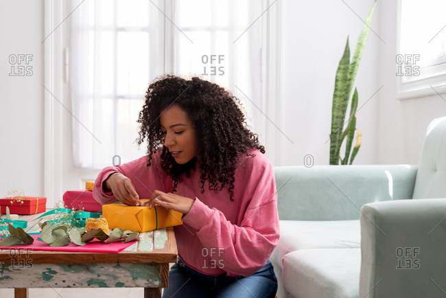Latin woman wrapping handmade craft gifts on the table at home