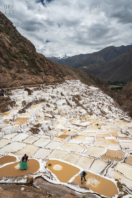 Peru - October 8, 2018: Elevated view of workers at Maras salt marsh terraces, Salinas de Maras, Cuzco Region, Peru