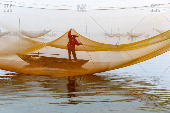 Fisherman working on the nets at sunrise, Thu Bon River, Quang Nam Province, Vietnam