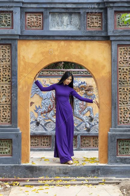 Vietnam - March 24, 2019: A Vietnamese woman in an Ao Dai dress at the Tu Duc Tomb, Hue,  Hue, Thua Thien-Hue province, Vietnam
