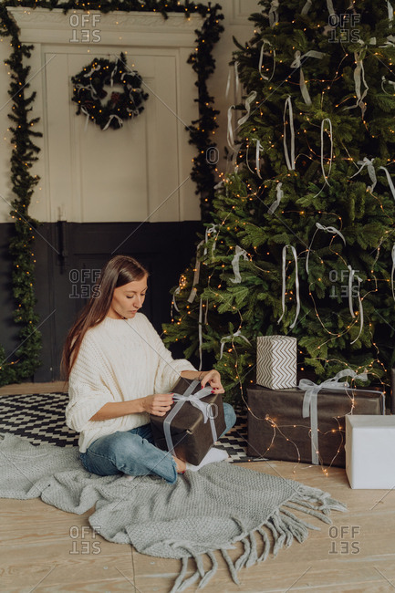 Young woman sitting by the Christmas tree wrapping gifts