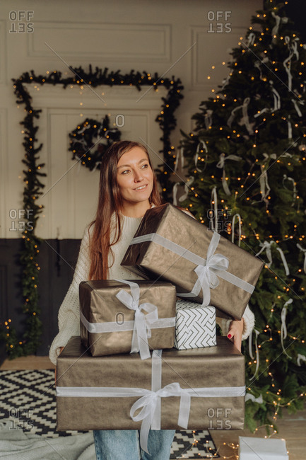 Woman carries large gifts over to the Christmas tree in preparation for the holidays