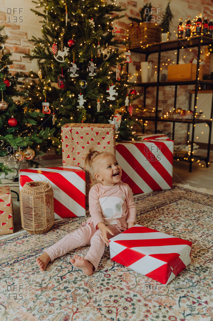 Young girl sits under the Christmas tree laughing while holding a large present