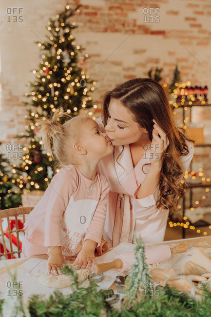 Woman kisses her daughter as they bake Christmas cookies in front of the Christmas tree