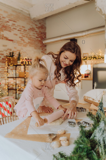 Woman helping her daughter with a rolling pin while making Christmas cookies