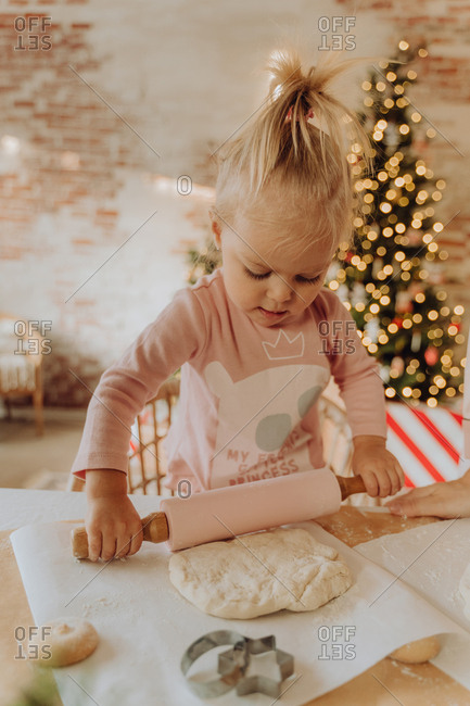 Young girl making Christmas cookies at the kitchen table