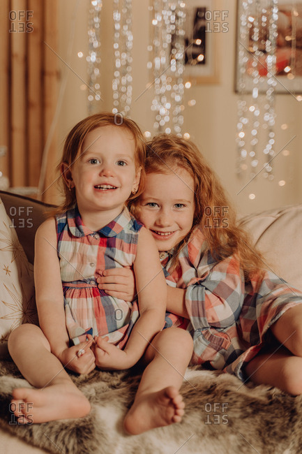 Two young sisters with red hair hugging and smiling with the holiday lights in the background