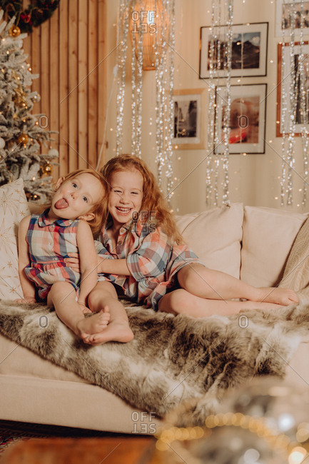 Two sisters playing and hugging on the couch with holiday lights in the background