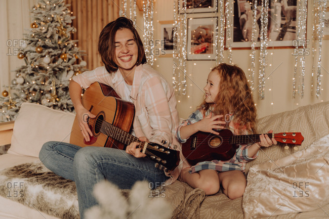 Woman laughing and playing guitar with her daughter