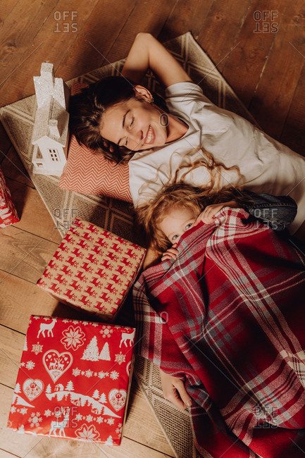Woman with a child laying next to the Christmas tree and covered with a blanket next to gifts