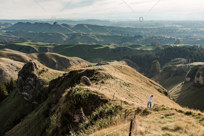 View over Te Mata Peak, Hawke's Bay, New Zealand with girl climbing downhill