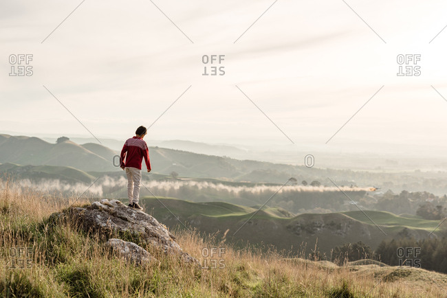 Young boy standing on rocky cliff at Te Mata Peak, Hawke's Bay, New Zealand