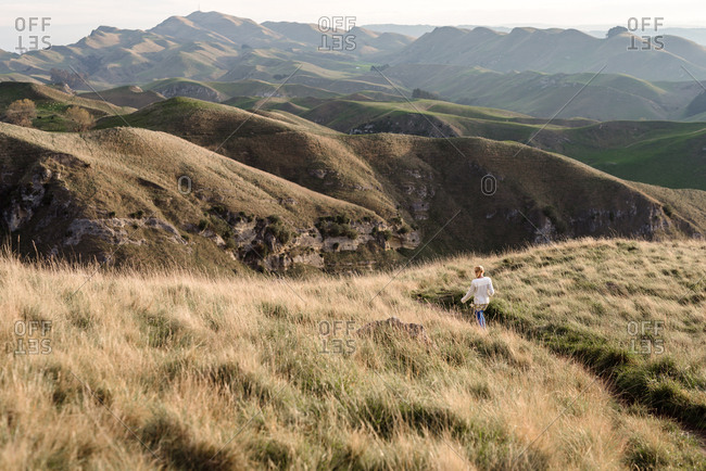 Back view of a girl walking on trail at Te Mata Peak, Hawke's Bay, New Zealand