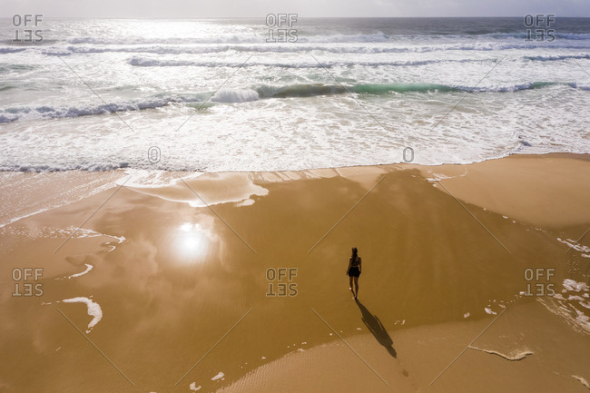 Aerial view of woman walking alone at hidden beach at Alexandria Bay, Australia.