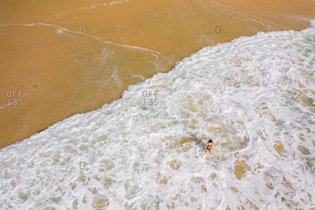 Aerial view of sexy woman at hidden beach at Alexandria Bay, Australia.