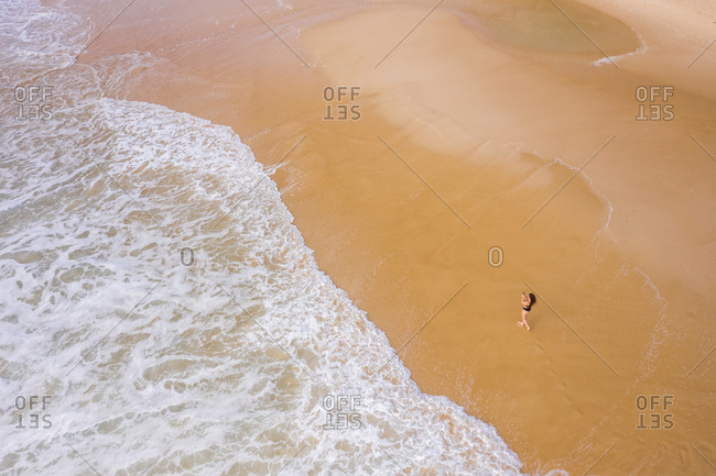 Aerial view of woman photographing at hidden beach at Alexandria Bay, Australia.