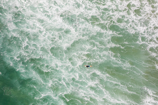 Aerial view of man surfing on the agitated sea at Alexandria Bay, Australia.