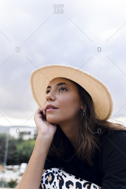 Portrait of fashionable young woman daydreaming outdoors