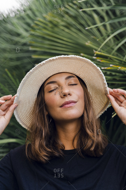 Portrait of young woman with eyes closed wearing summer hat