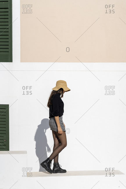 Young brunette woman wearing sun hat and walking on a white wall