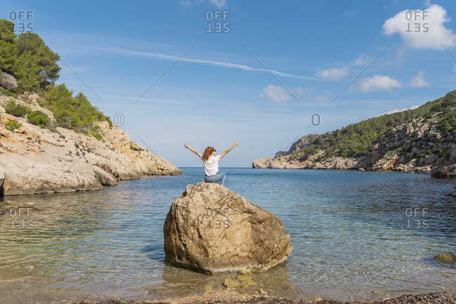 Redheaded woman with raised arms sitting on rock at the beach