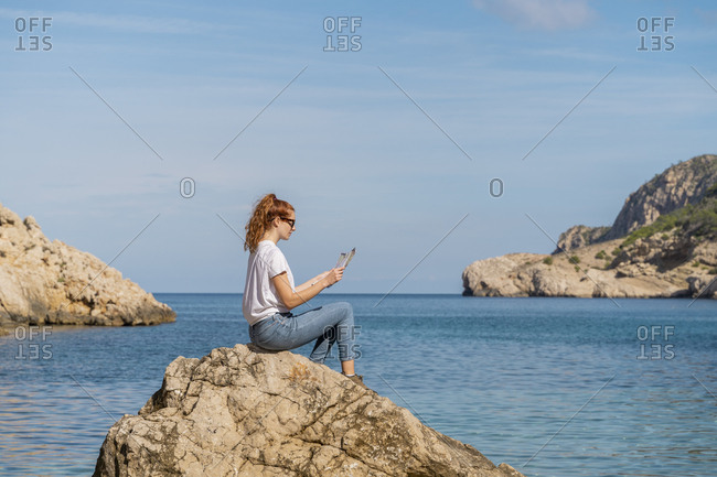 Redheaded woman sitting on rock and reading magazine