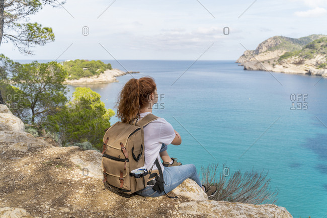 Redheaded woman sitting on viewpoint and looking at distance- Ibiza