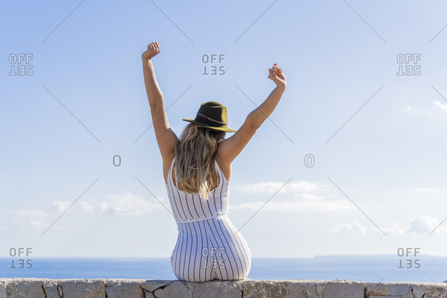 Young woman sitting on a wall with raised arms and looking at distance- viewpoint in Ibiza