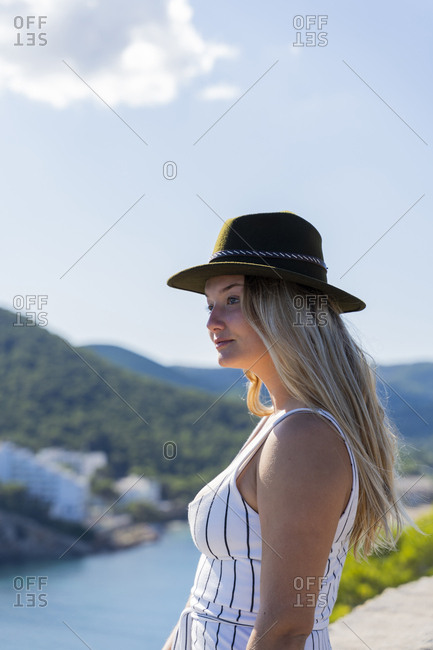 Young woman sitting on a wall and looking at distance- viewpoint in Ibiza