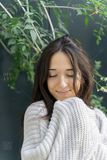 Young woman with closed eyes wearing a cardigan