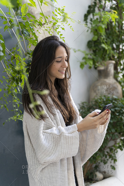Young woman wearing cardigan and using smartphone