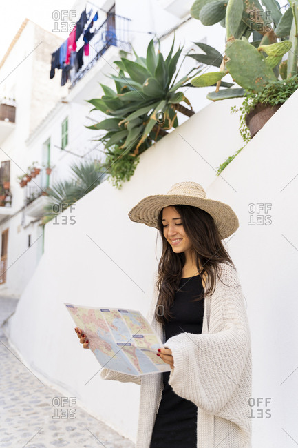 Young woman wearing sun hat and looking on map