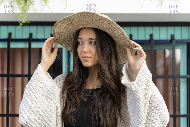 Young woman wearing sun hat and looking sideways