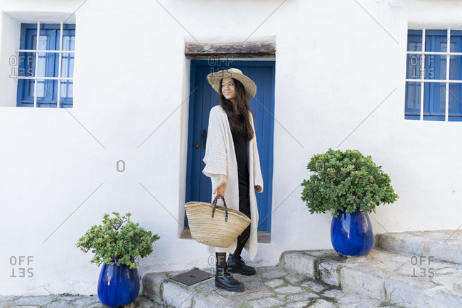 Young woman wearing sun hat and cardigan in front of a blue door