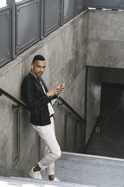 Portrait of man standing on stairs of underground station using earphones and smartphone