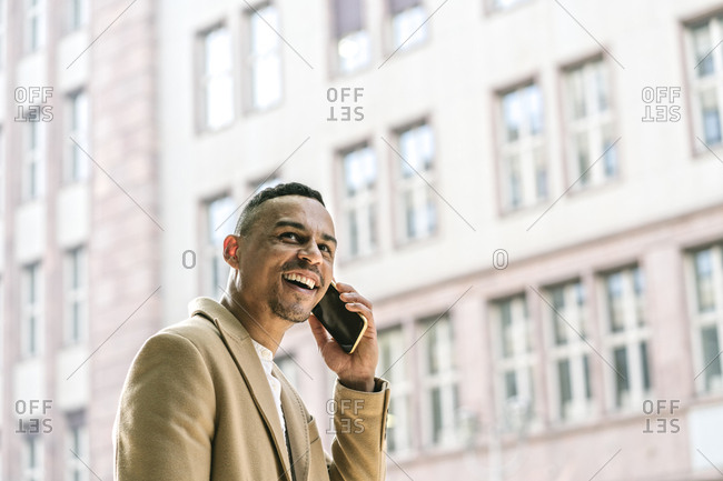 Portrait of laughing businessman on the phone in the city