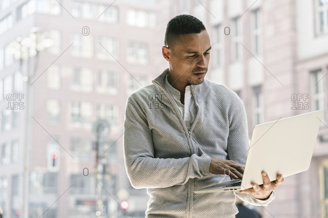Portrait of businessman in the city using laptop