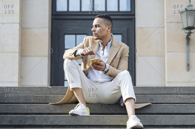 Businessman with smartphone sitting on stairs in the city