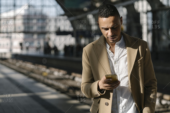 Businessman standing on platform of train station  using smartphone- Berlin- Germany