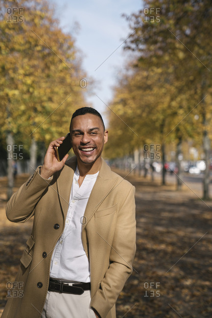 Portrait of laughing businessman on the phone in autumn