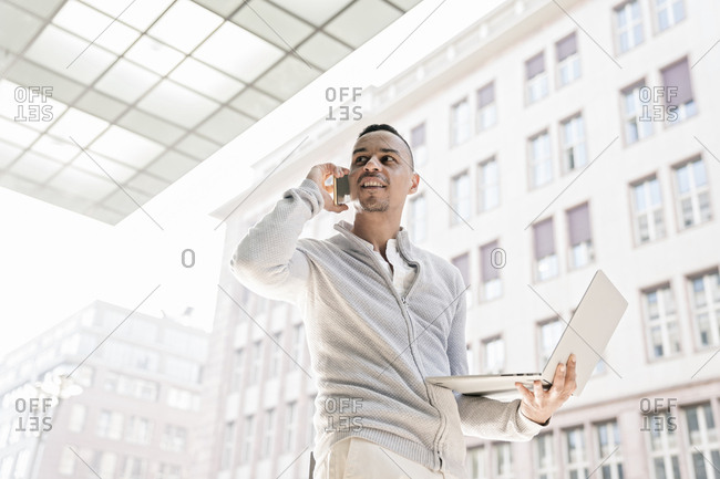 Portrait of businessman on the phone holding laptop looking at distance