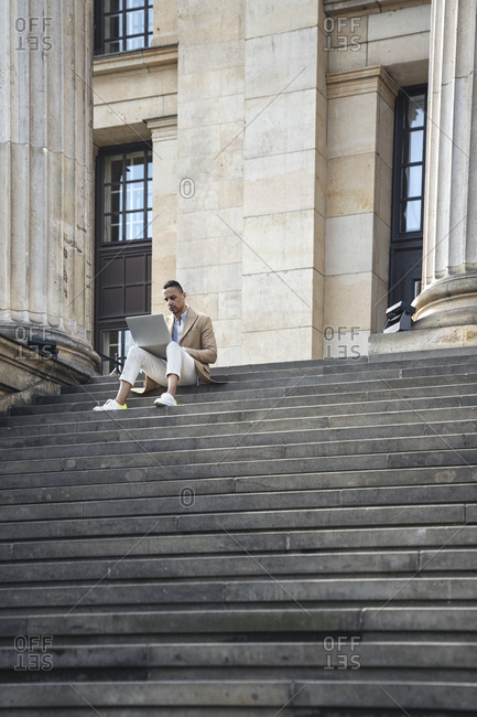 Businessman sitting on stairs using laptop